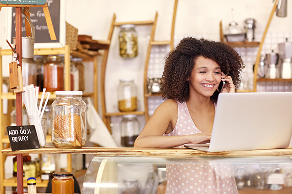 Smiling coffee shop owner typing on a laptop while talking